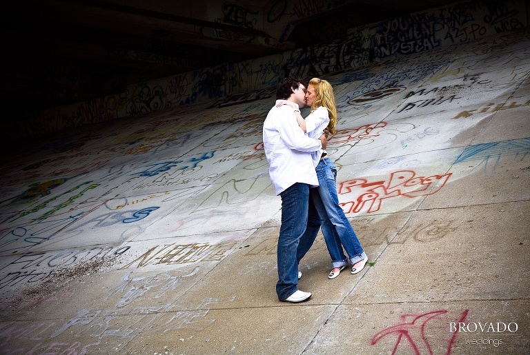 Couple kisses on graffiti covered overpass