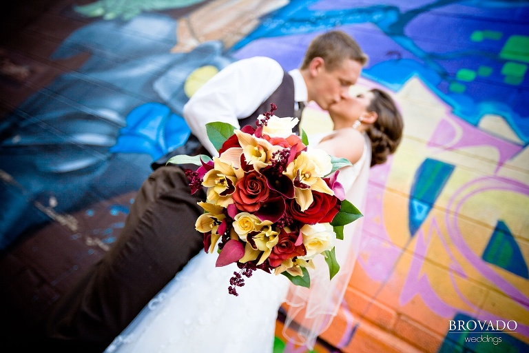 bouquet takes up the foreground while the bride and groom kiss in the background