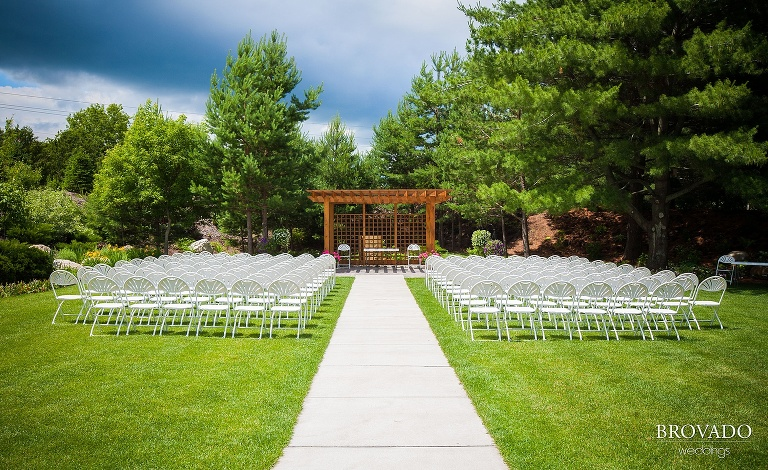 white wedding ceremony chairs set up on a green lawn