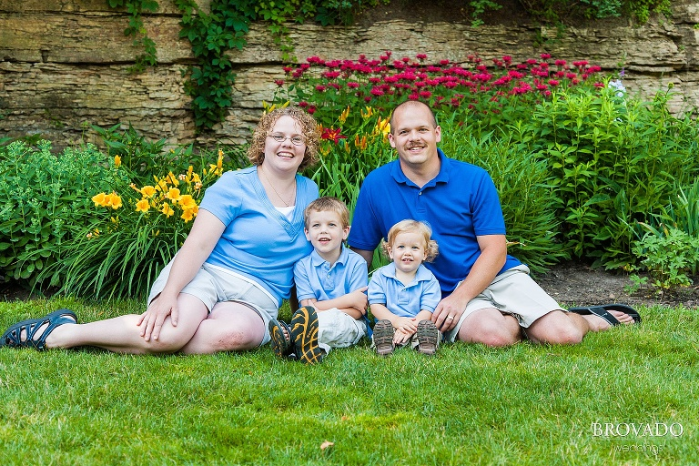 family all in blue sits together on grass