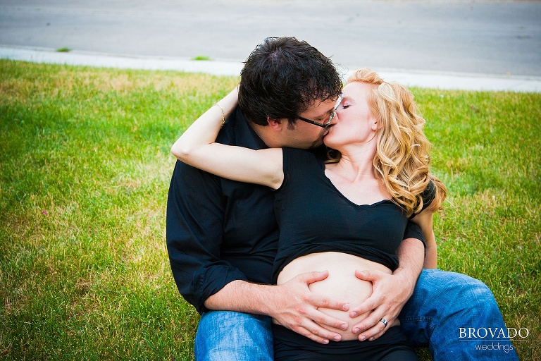 husband holds his wife's pregnant belly