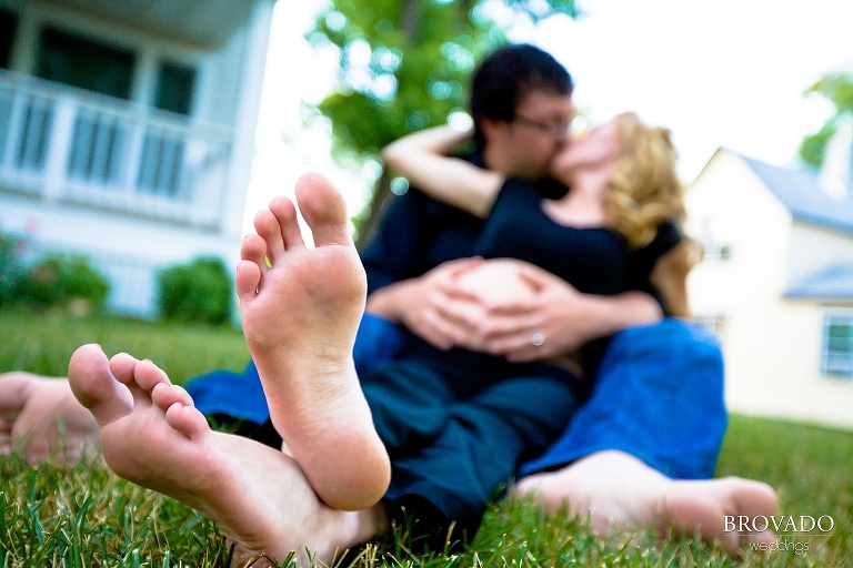 maternity photo shows couple kissing with woman's feet in foreground