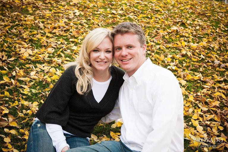 couple sit among fall leaves