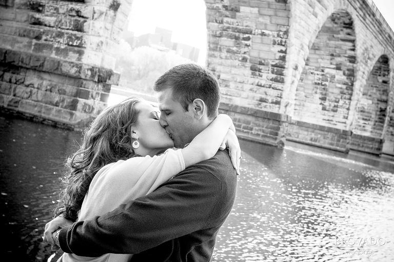 couple kiss under stone arch bridge