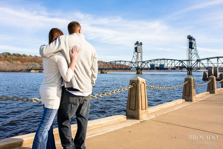engaged couple embraces in front of stillwater lift bridge