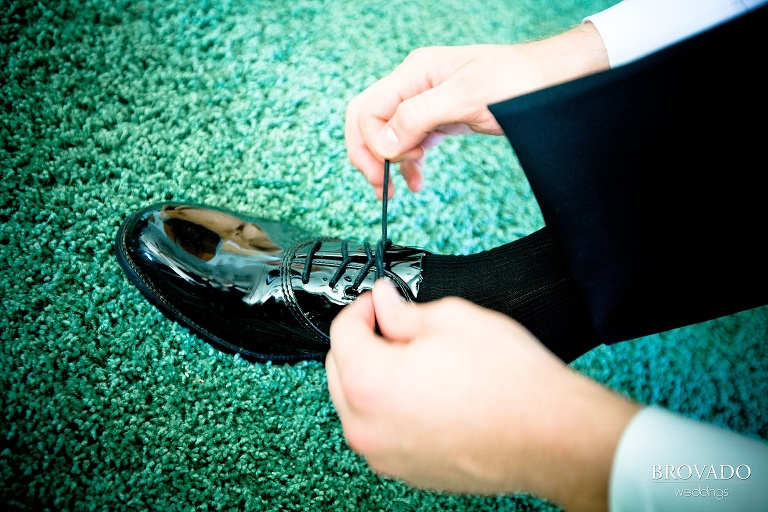 close up of groom tying his shoes