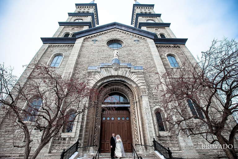 bride and groom in front of assumption catholic church
