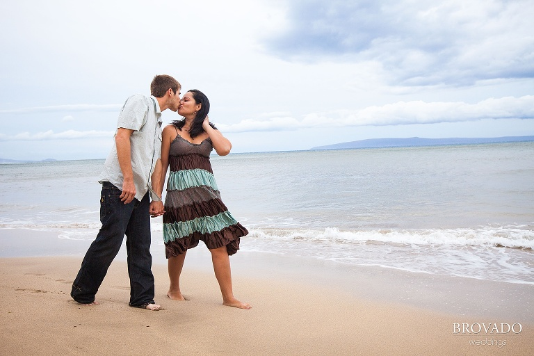 couple stops on the beach to kiss in front of the ocean