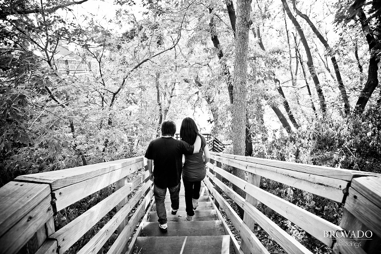 couple walking down wooden steps in black and white engagement photograph