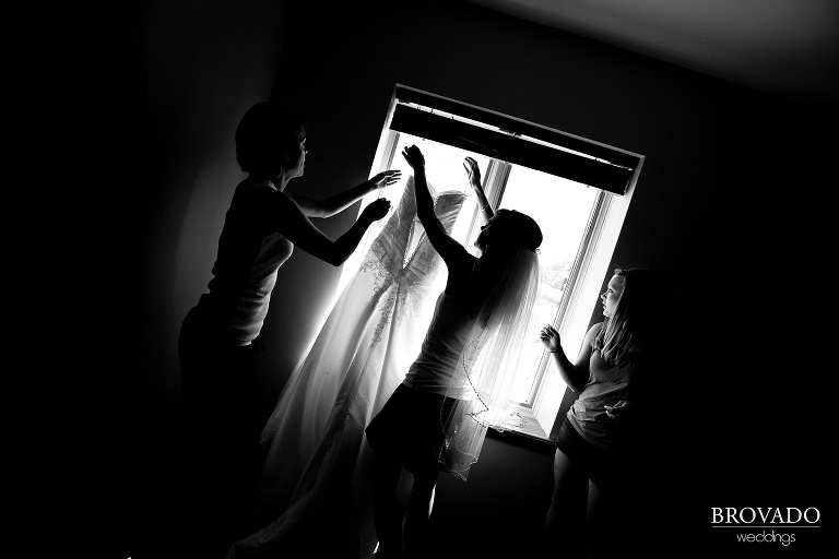 black and white photograph of bride holding up her wedding dress