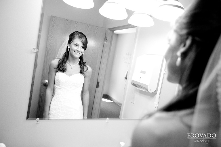 black and white photograph of bride smiling in a mirror