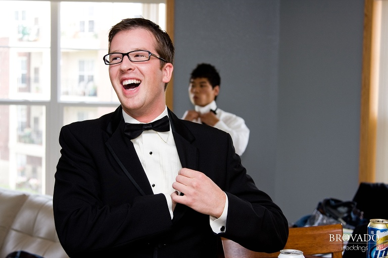 groom laughing while he adjusts his tuxedo