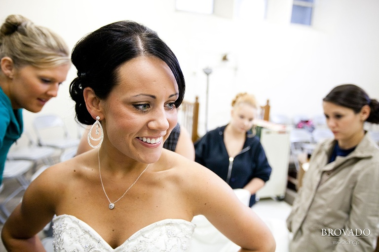 close up of bride while her bridesmaids zip up her dress