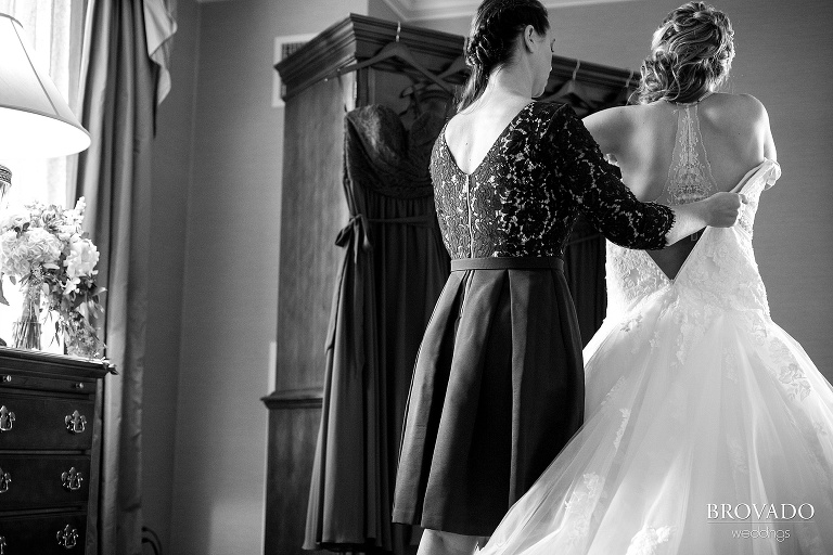 Bride gets help putting on her wedding dress