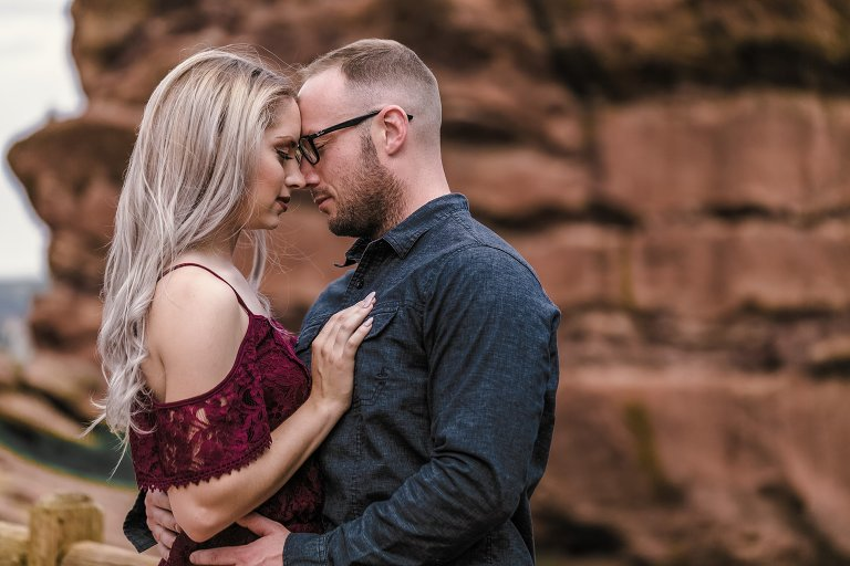 Couple posing in front of colorado red rocks