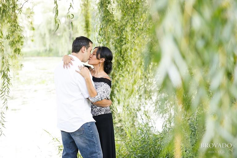 Christine and Nick kissing among willow trees