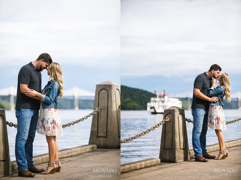Engaged couple kissing in front of boat on the st croix