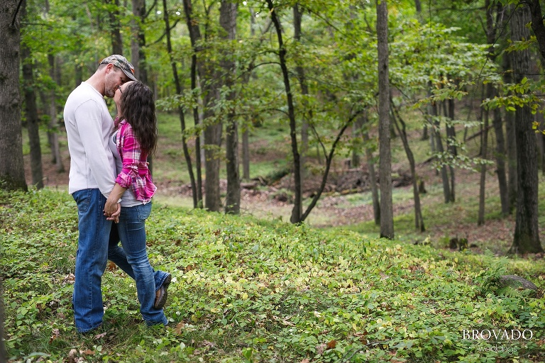Cute engagement of couple kissing in the woods