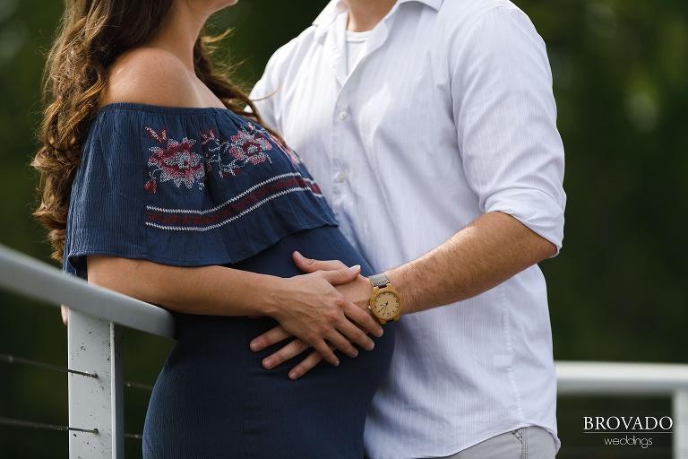 Closeup of John's hand on Nova's pregnant belly