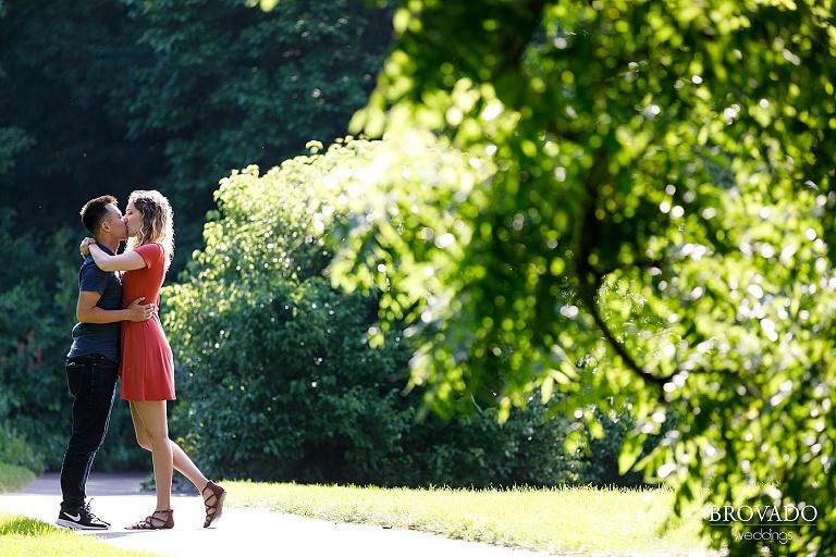 Engaged couple kissing at MN landscape arboretum