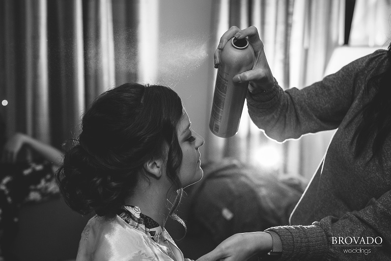 Black and white image of bethany having her wedding updo hairsprayed